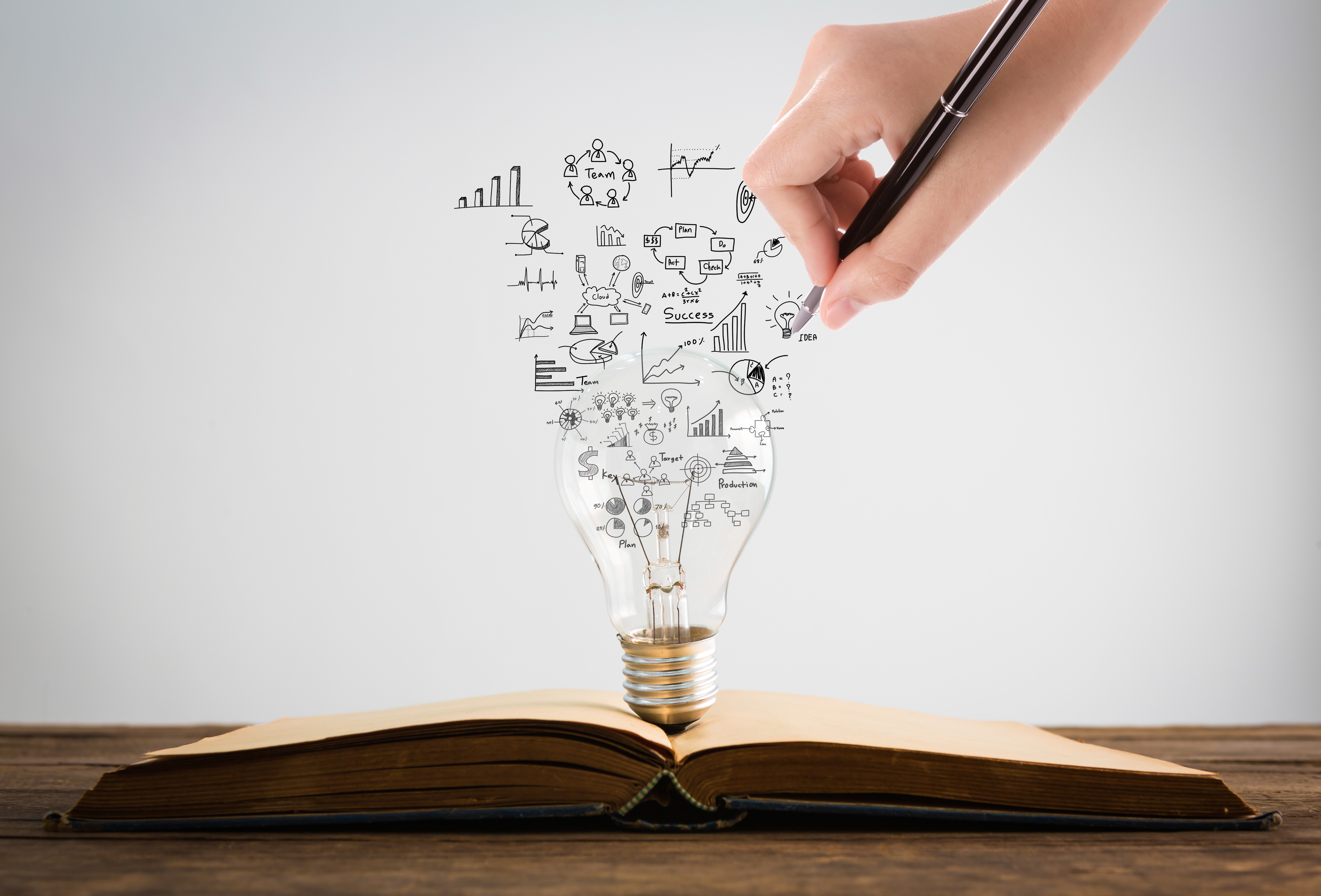 Book and light bulb with hand drawing graph